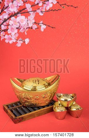 Chinese gold ingot and abacus with Chinese calligraphy mean symbols of wealth and prosperity.