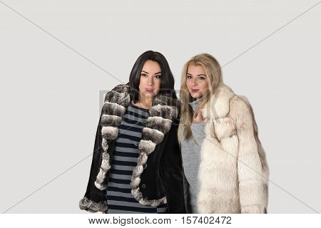 two girlfriends blonde and brunett in short fur coats walk