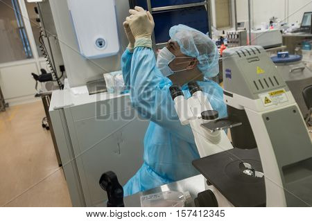 Saint-Petersburg Russia - November 16 2016: A member of the laboratory of department of Advanced Studies biotech companies Biocad at work at the microscope behind glass in a sterile clean room