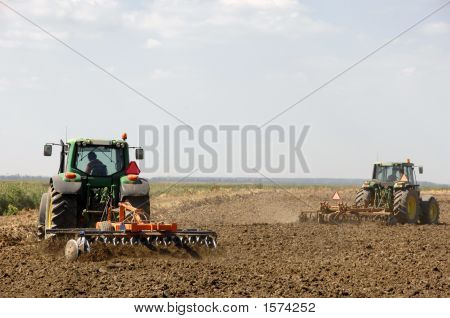Farmers Plowing With Tractor