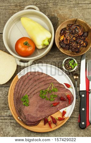 Cold roast beef on a wooden table. Delicacy of beef. Preparing cold refreshments. Traditional meal. Beef roast beef with green pepper and chili peppers and vegetables.