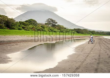 Volcanic landscape of the Ometepe Island, Nicaragua. Very active Concepcion volcano is fuming on the background with the lake beach on the foreground