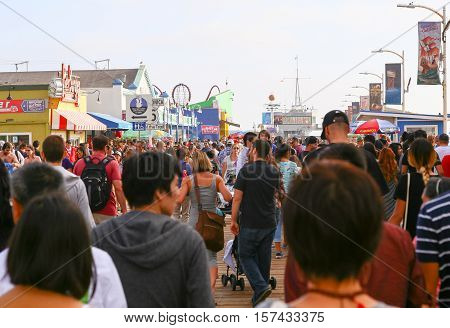SANTA MONICA, USA - MAY 30, 2015: Crowded Santa Monica Pier and Pacific Park with food stands gift shops fun rides and the harbor office in the back.