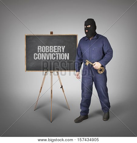 Robbery text on blackboard with thief and key