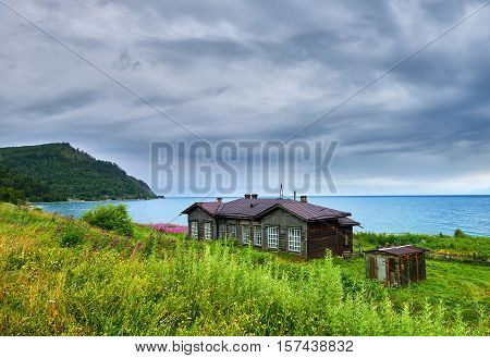 PONOMOREVKA IRKUTSK REGION RUSSIA - July 28.2016: Old barracks since construction of Circum-Baikal railway on 107 kilometer of road. Good condition of house is supported by residents. In background Lake Baikal and Cape Ivanovo