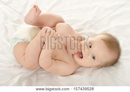 Adorable baby boy lying in pampers on blanket on a white background