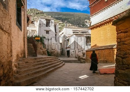Old woman walking in the courtyard of the Jokhang monastery near Lhasa in central Tibet.