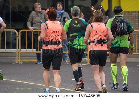 VALENCIA, SPAIN - NOVEMBER 20, 2016: Women running with funny t-shirt don't follo me I'm lost marathon, November 20, 2016 in Valencia, Spain