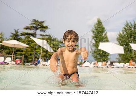 Cute little boy kid child splashing in swimming pool having fun leisure activity