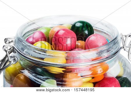 Colorful candies and chewing gum in glass jar