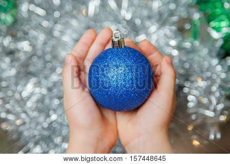 Girl gives a christmas tree ball. Christmas-tree decoration in girl's palm