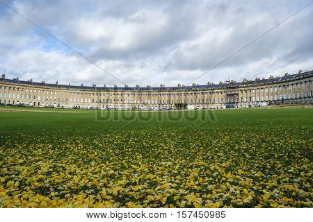 Autumnal scene of fallen leaves on the grass in front of the impressive sweep of Georgian architecture of Royal Crescent in Bath England with cloudy sky