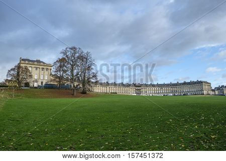 Autumnal scene of the impressive sweep of Georgian architecture of Royal Crescent in Bath England with cloudy sky and fallen leaves on grass