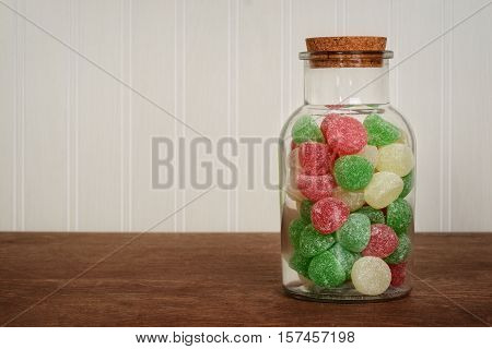 jar of christmas gum drops on a wood table