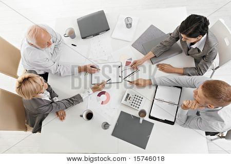 Businesspeople working together at meeting, discussing document on clipboard, high angle view.?
