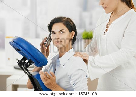 Occupied businesswoman talking on mobile while getting neck massage in office.?