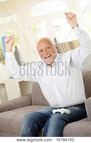 Senior man happy winning computer game, raising arms, laughing, looking at camera.?