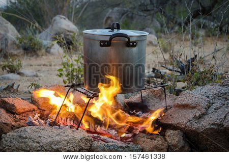 Aluminium pot standing on foldable grill being heated over outdoor camp fire surrounded by rocks.