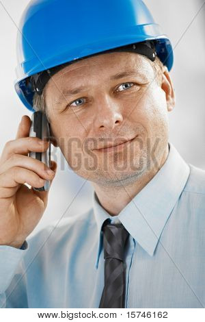 Closeup portrait of architect wearing hardhat, talking on mobile, looking at camera.?