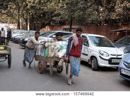 DELHI, INDIA - FEBRUARY 13 : Hard working indians pushing heavy load through streets of Delhi, India on February 13, 2016. Human labour is still cheaper than motorised vehicles.