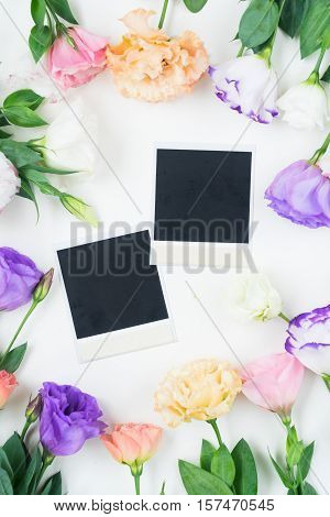 Pink, white and violet eustoma flowers frame with two instant photos