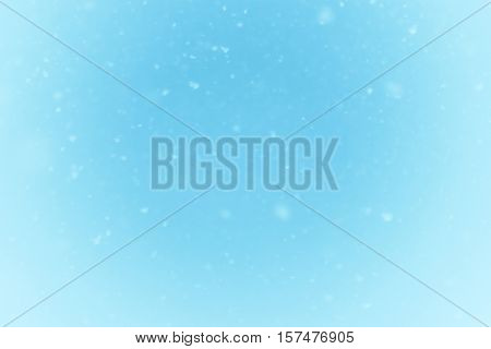 Winter falling snow on blue background. Real natural photo
