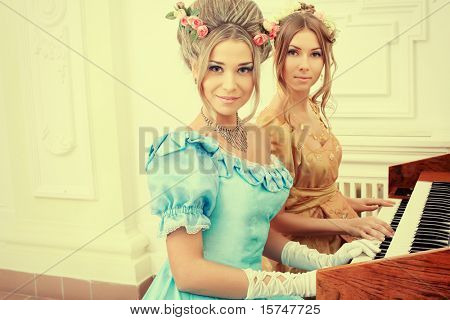 Two beautiful women in medieval era dresses playing the piano.