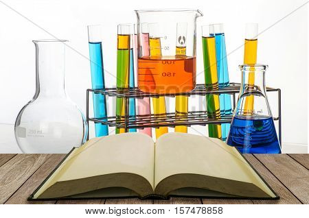 Open Book On Wooden Table With Science Laboratory Test Tubes Background