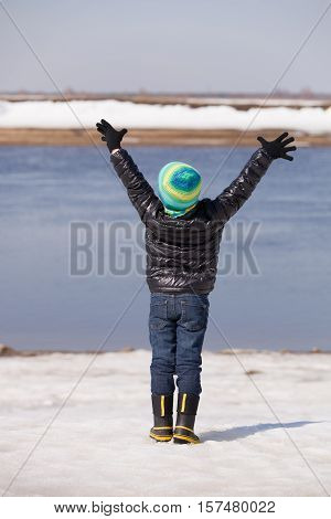 Back view on a cute happy kid boy standing on the river shore with his hands up on sunny winter day. Child walking by the sea and having fun. Lifestyle concept.