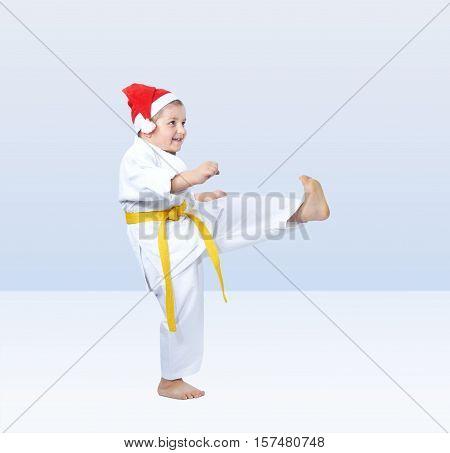 Sportsman is beating kick leg on the light background