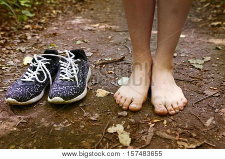 bare feet stay tiptoe and trainer shoes close up photo on the forest path