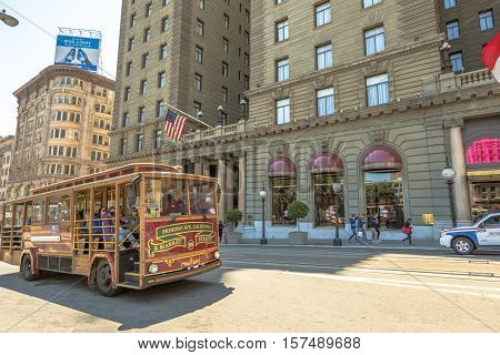 San Francisco, California, United States - August 17, 2016: Classic cable cars on wheels with guided tour carrying tourists in front of Westin St. Francis hotel along the famous Powell Street.