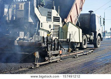 Paver machine laying asphalt, fed by a dump truck
