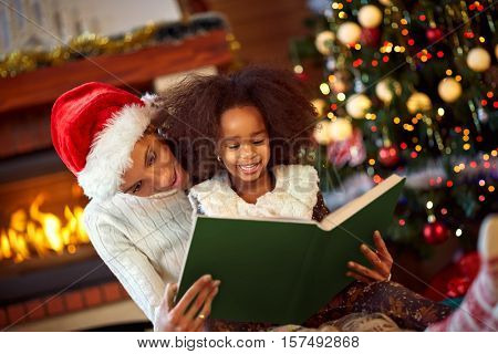 Pretty young mother reading a book to her daughter near Christmas tree, merry Christmas