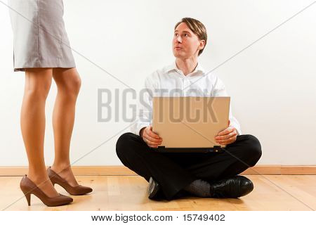 Businesspeople at home; he is sitting with laptop on the floor