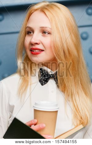 Dreamy ginger girl in white shirt with bow tie holds coffee in hands close-up on blue background