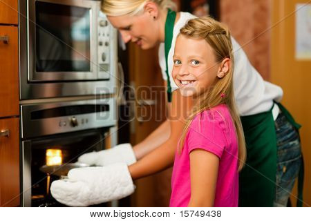 Mother and daughter cooking � they are putting roast in the oven
