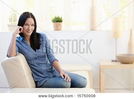 Portrait of attractive young woman sitting on couch at home, looking at camera, smiling.?