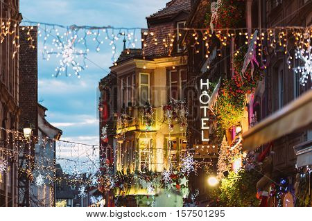 Hotel neon sign on romantic luxury building above colorful Christmas Market atmosphere with people silhouettes walking on illuminated street with Christmas toys and decorations in oldest Christmas Market worldwide Strasbourg
