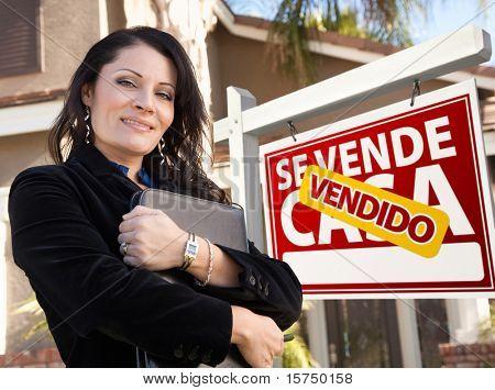 Orgulloso, atractivo agente femenino hispano frente Español Vendido Se Vende Casa bienes raíces muestra una