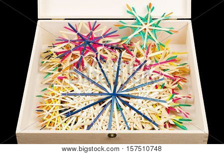 Straw stars Christmas decoration in wooden box. Handmade colorful decor for windows, as gifts or to hang on the xmas tree, traditionally made from natural straw. Front view photo on black background.