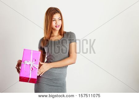 Occasions gifts people concept. Beautiful woman with pink gift. Young blonde lady wearing nice gray outfit top and skirt. Girl is mixed race.