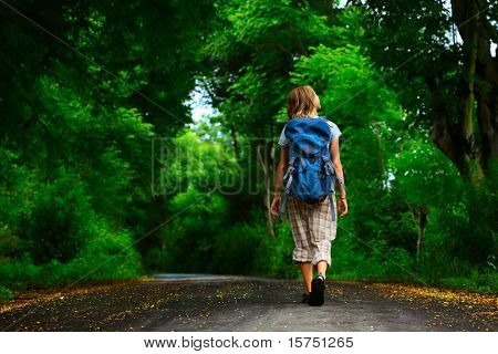 Young woman with backpack walking on a wet asphalt path in a park
