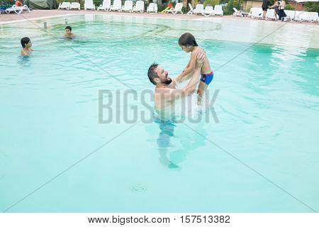 Young boy kid child splashing in swimming pool having fun leisure activity