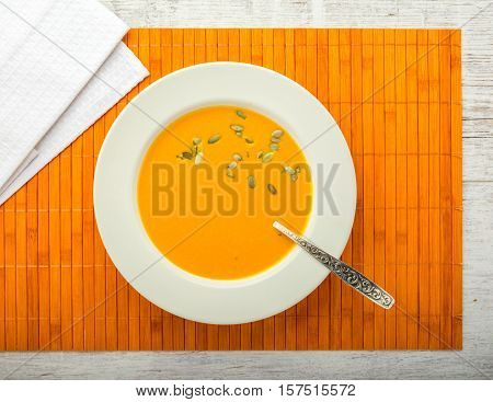 pumpkin cream soup with pumpkin seeds in a white plate with a spoon on a orange napkin closeup top view