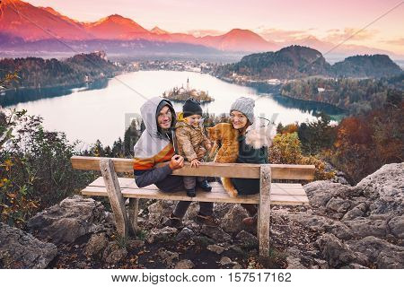 Family travel Europe. Bled Lake at autumn or winter time Slovenia Europe. Top view on Island with Catholic Church in Bled Lake with Castle and Mountains in Background.