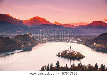Amazing View On Bled Lake. Autumn or Winter in Slovenia Europe. Top view on Island with Catholic Church in Bled Lake with Castle and Mountains in Background.