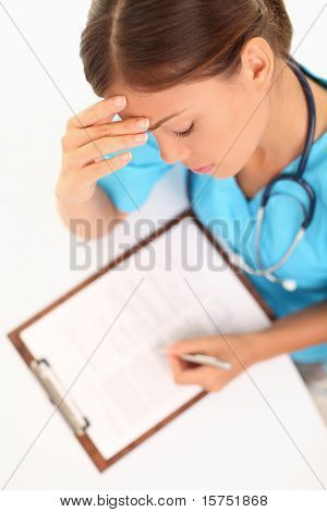 Medical doctor or nurse working concentrating writing medical report or journal. Young multi-racial asian caucasian woman.