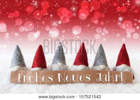 Label With German Text Frohes Neues Jahr Means Happy New Year. Christmas Greeting Card With Red Gnomes. Sparkling Bokeh And Christmassy Background With Snow And Stars.