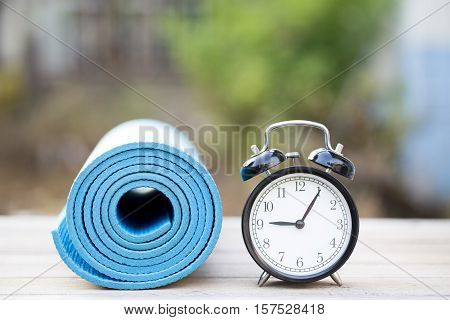Time for exercising clock and yoga mat outdoor